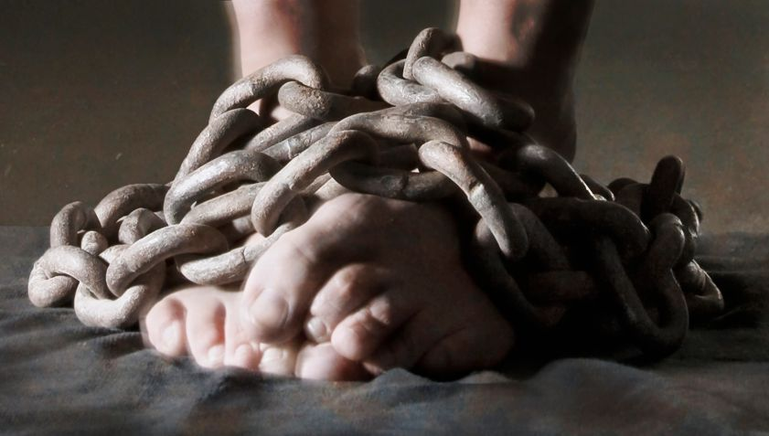 Close-up of bare feet bound in heavy metal chains