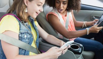 Teenage girls in car distracted by mobile phone