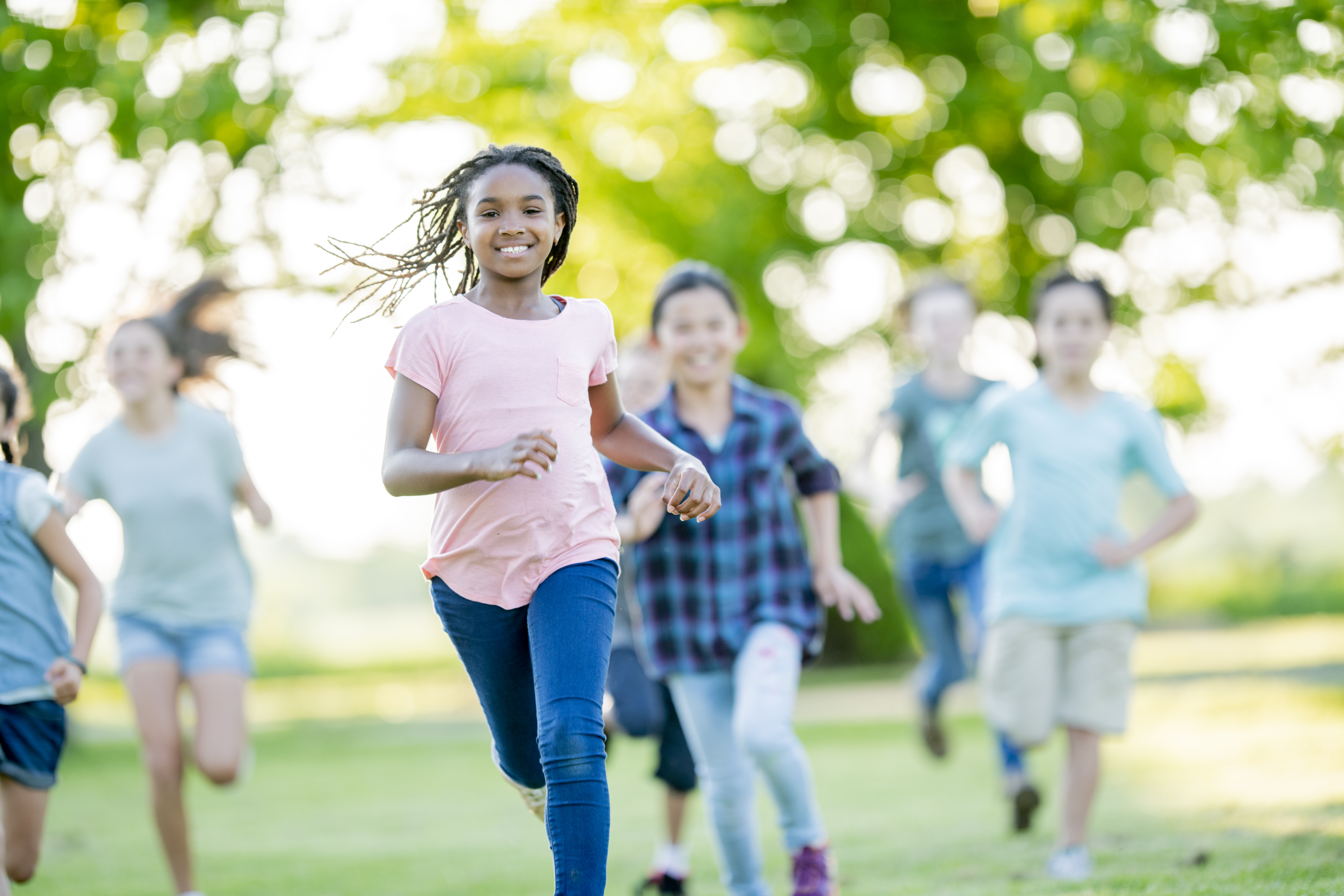 African American girl smiling while running through the park with her friends
