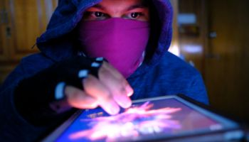 young hacker with digital tablet stealing information- data security theft idea