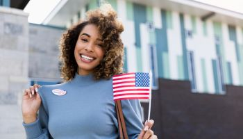 "Woman smiles for camera and shows off ""I voted"" sticker"