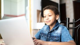 Child boy studying using laptop at home