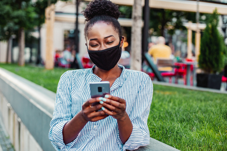 African American woman with mask using phone